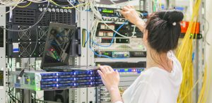 lady working with networking banks of computers